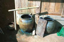 to Jpeg 27K Large earthenware pots holding indigo dye liquid in a Yao village in the hills around Chiang Rai 8812q11.jpg