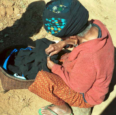 An old Yao lady sitting in the sun sewing a gusset into a jacket 8812q18.jpg