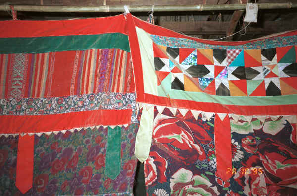 Jpeg 40K Headings to curtains (or just possibly mosquito nets) separating sleeping from living areas in a Black Thai house.  Note the woven fabric in the heading to the left and patchwork in the heading to the right.  The hanging tabs echo those on some of the baby carriers.  Dien Bien Phu, Lai Chau Province.  9510D15.JPG