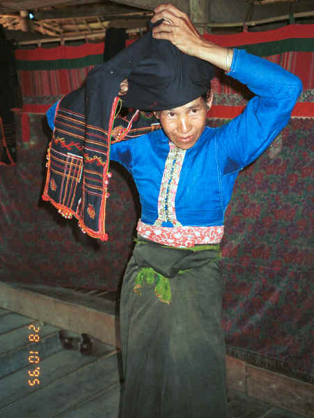 Jpeg 33K Black Thai lady showing how her head cloth is worn.  Note the curtains behind shielding off the sleeping areas from view and with hand woven cloth pieced into the heading area of the curtains.  Dien Bien Phu, Lai Chau Province 9510D23.JPG