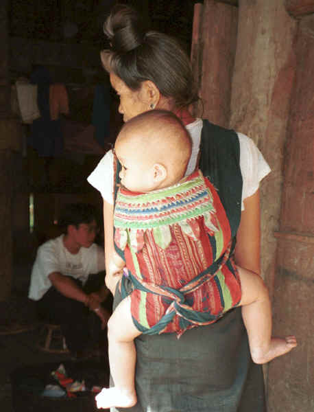 Jpeg 26K Black Thai baby being carried on it's grandmother's back in a baby carrier made with an insertion of supplementary woven cloth and layers of edging made from individually folded 'points'.  A village near Dien Bien Phu, Lai Chau Province. 9510E21.JPG