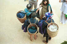 to Jpeg 49K Black Hmong women trading old clothing with western tourists in the streets of Sa Pa, Lao Cai Province.  Some of the clothing has been over-dyed with turquoise or purple chemical dyes. 9510H34.JPG