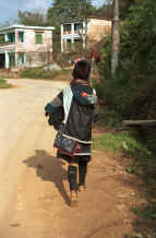 to Jpeg 31K Black Hmong Woman carrying her baby home from Sa Pa, Lao Cai Province in an embroidered and batiked baby carrier  9510I23.JPG