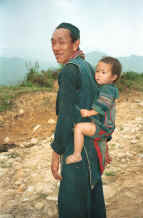 to Jpeg 30K Black Hmong man with a young girl - probably his granddaughter - in a baby carrier on his back, in the hills around Sa Pa, Lao Cai Province.  9510I28.JPG