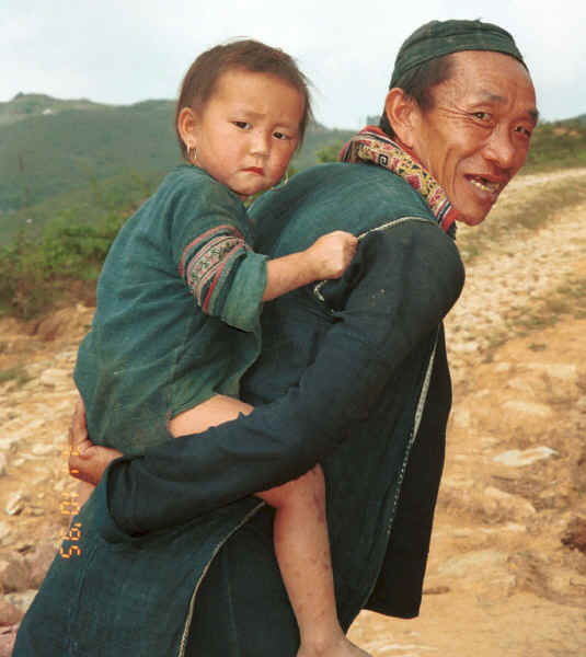 Jpeg 30K Black Hmong man with a young girl - probably his granddaughter - on his back, in the hills around Sa Pa, Lao Cai Province.  Note the beautifully embroidered collar back on his sleeveless indigo dyed jacket. 9510K13.JPG