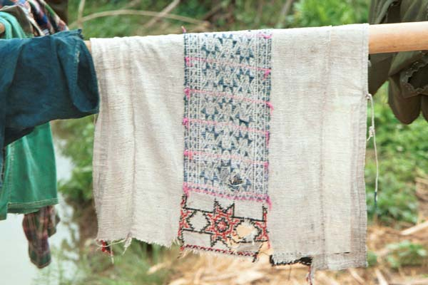 Jpeg 39K 9511A11 Dao Quan Trang woman's bodice hanging out to dry and showing the reverse side of the embroidery with the characteristic stars at the base. The background fabric appears to be hand spun and woven and is probably cottton. Luong village on the road from Sa Pa to Lao Cai town, Lao Cai province.