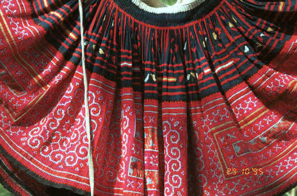 Detail of Red Hmong (Lai Chau province, northern Vietnam) woman's skirt showing the waist gathering, applied strips of red fabric and small triangles to the top border and cross-stitch with applied floral rectangles in the bottom border 9510f27.jpg