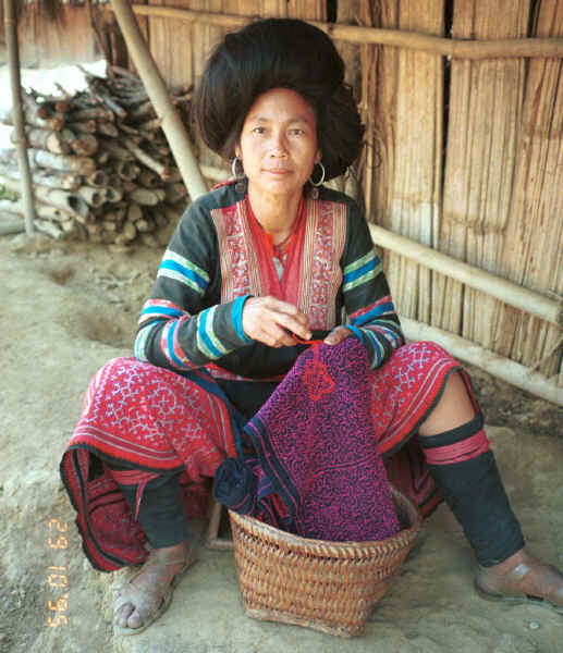 Red Hmong woman working (from the back) on the cross-stitch border of the bottom band of a new skirt similar to the one which she is wearing. 9510f31.jpg