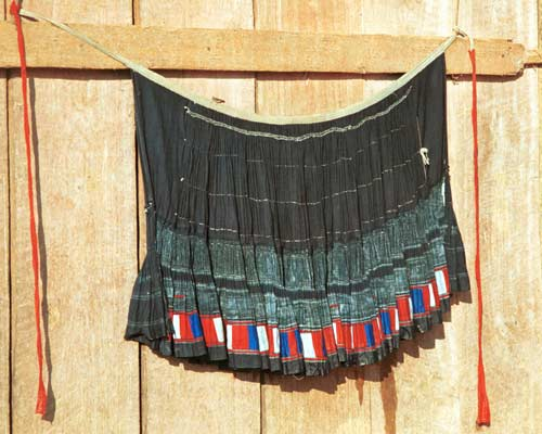 Jpeg 35 K 9510G19 Flowery Hmong woman's short pleated skirt hanging out to dry outside a house in small road-side village near Phong Tho (Phong Thanh) in Lai Chau Province. The skirt is dyed a dark indigo after very many dippings in the dye vat.  Note the inserted strip of wax resist fabric and the strip of pieced red, blue and white fabric squares from purchased fabric