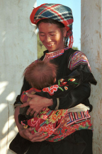 Jpeg 53K 9510G27  Flowery Hmong mother with her baby outside a house in small road-side village near Phong Tho (Phong Thanh) in Lai Chau Province.