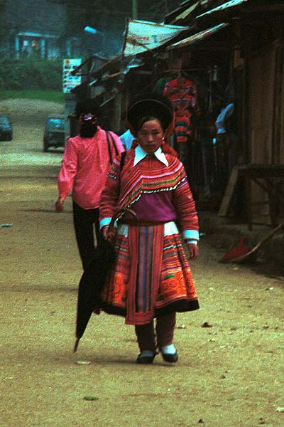 Jpeg 48K 9510K26  Brightly dressed Flowery Hmong woman walking down the street in Sa Pa, Lao Cai Province.  She is a visitor to Sa Pa, in the town on a training programme, and lives near the Chinese border. The Flowery Hmong near to the border tend to wear more bought trimmings on their clothing which they obtain from China.  Note her embroidered and applique leg wrappings and her long apron.  She only very narrow bands of wax resist on her skirt which features applied strips of fabric and embroidery.