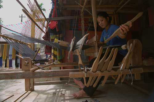 Jpeg 31K mc4 Thu weaves fabric on the loom beneath her house which she shares with all the women in her family. The Mai Chau valley, Hoa Binh Province, northern Viet Nam.